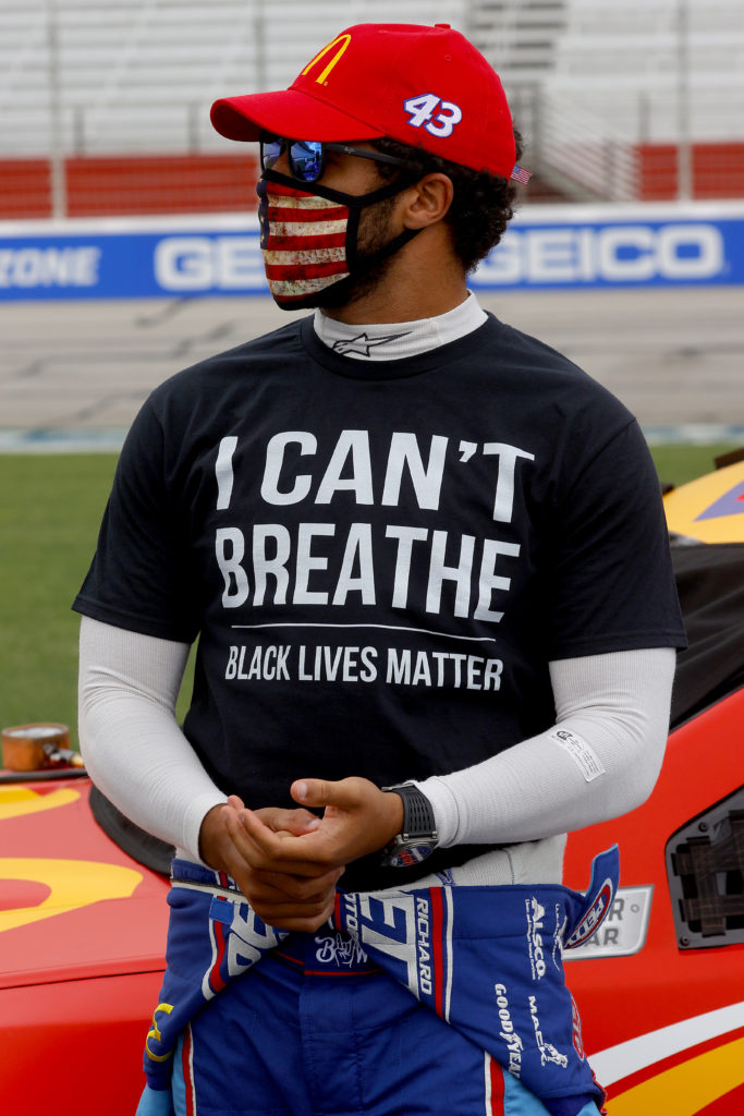 "HAMPTON, GEORGIA - JUNE 07: Bubba Wallace, driver of the #43 McDonald's Chevrolet, wears a ""I Can't Breath - Black Lives Matter"" T-shirt under his fire suit in solidarity with protesters around the world taking to the streets after the death of George Floyd on May 25 while in the custody of Minneapolis, Minnesota police on the grid prior to the NASCAR Cup Series Folds of Honor QuikTrip 500 at Atlanta Motor Speedway on June 07, 2020 in Hampton, Georgia. (Photo by Chris Graythen/Getty Images)"